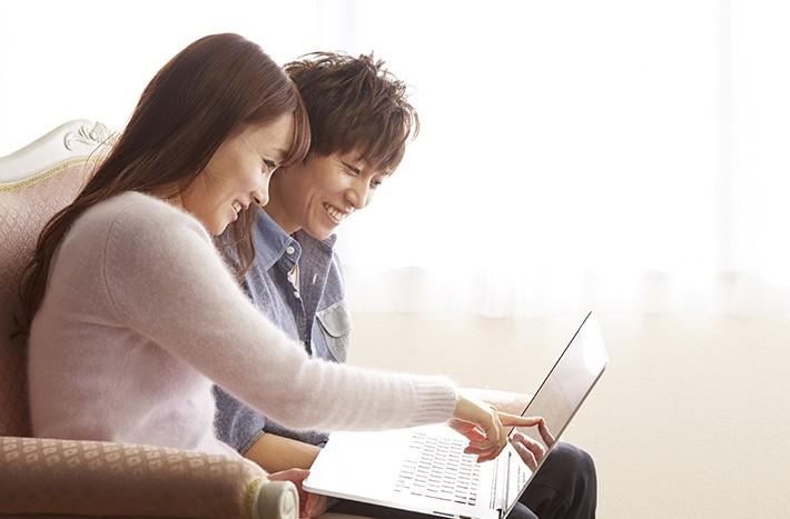 ノートパソコンを見る夫婦・カップルのイメージ画像