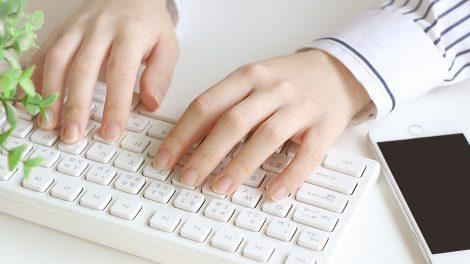 パソコンで仕事をするママの手